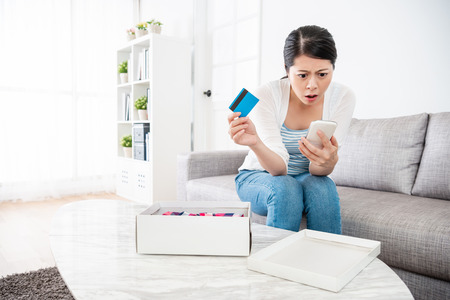 woman sitting at home with a doubtful face, she is unsatisfied with her purchase which buys from the e-shop Banque d'images