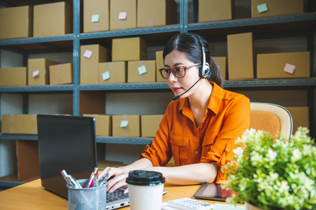 professional receptionist is wearing headset, talking to client and helping them to solve their online shop problem 写真素材
