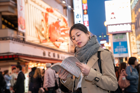 elegant female tourist is going to the next spot to see the night view by her map after dinner Imagens - 110479231