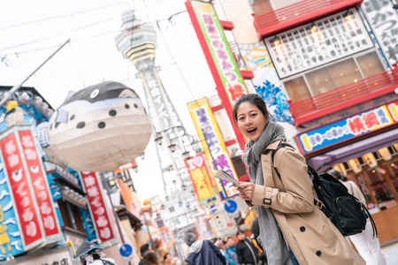beautiful tourist holding the map and checking next spot of her journey, face to camera smiling.background is Tower Reaching Heaven