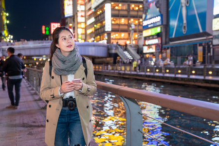 beautiful female photographer feel really full and relaxing walking around the river after dinner