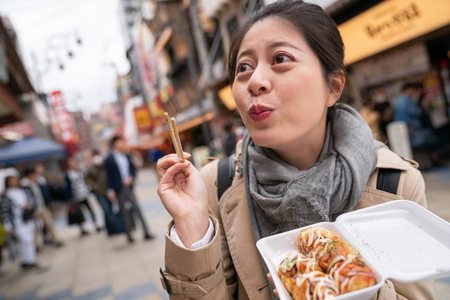beautiful woman is so excited when she ate takoyaki because its too tasty that she feels she is in the heaven