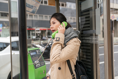 beautiful woman standing in the phone box and using public phone because she forgot her cell phone at home