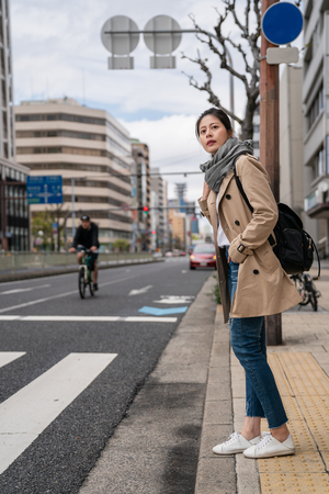 beautiful woman standing and waiting to cross the road. she is wearing a grey scarf Banco de Imagens