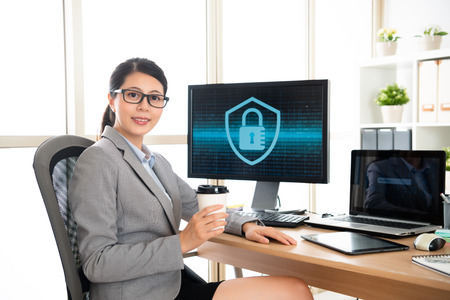elegant female office worker holding coffee sitting in front of office desk and looking at the camera when working