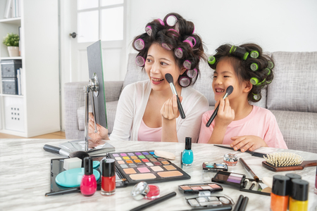 elegant young mom is teaching her cute little daughter how to do makeup 스톡 콘텐츠 - 109855902