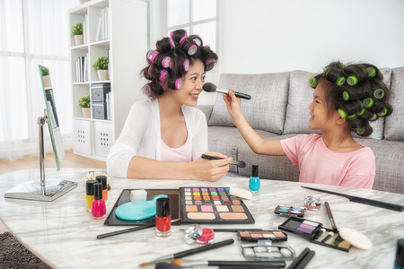 happy elegant lady feeling cheerful when her kid using brush helping her makeup with colorful cosmetic powder.