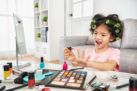 pretty little girl using moms cosmetics and nail polishes when her mom is not at home