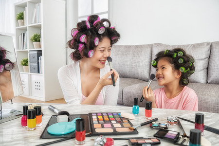 happy mom and little girl doing makeup together at home, they look at each other and smile happily