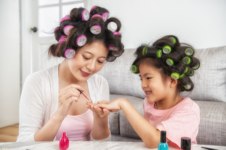mom using pink nail polish to paint her cute daughters nail to make her happier and prettier 스톡 콘텐츠