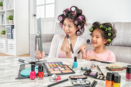 cute little daughter is learning makeup while her elegant young mom is doing makeup Stock Photo