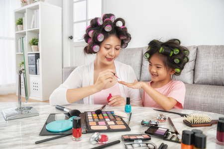 mom helping to make her daughters nail colorful and they are happily sitting at home Stock Photo