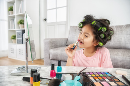 happy little girl doing makeup to make herself look like an adult