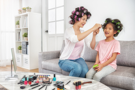 mom helping to set her daughters hair curly at home