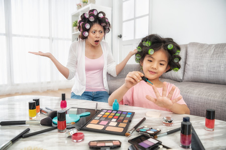happy young girl painting her nail herself and her mom behind her is really angry Foto de archivo - 109855918