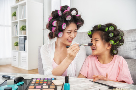 beautiful mom painting her cute daughters face by brush, they look cheerfully in the living room