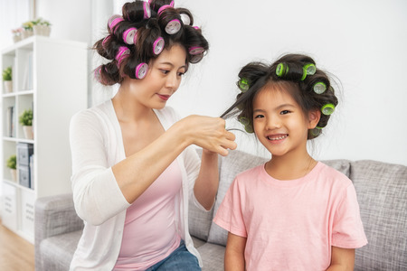 lovely mom and kid sitting in the living room and mom is setting daughter's hair 스톡 콘텐츠 - 109855937
