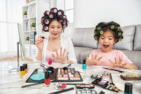 happy mom and little girl sitting at home together and paiting their nails themselves