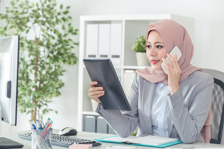 Muslim female employee contacting customers by cell phone and holding digital tablet. Freelance remote work at home or customer service support. Businesswoman lifestyle.