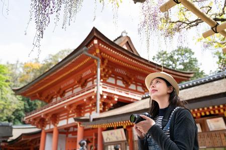 an elegant female traveler taking photo of the flowers by her slr camera