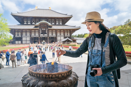 a pretty female photographer experience the Japanese traditional culture, she is burning the incense stick