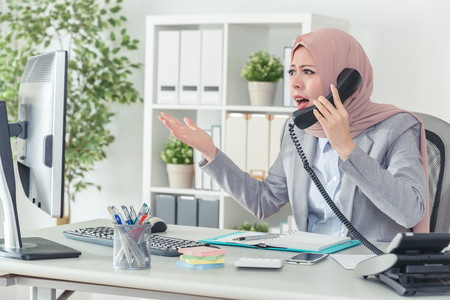 Muslim office lady is talking on the phone and fighting with her annoyed customer. businesswoman angrily arguing by telephone in office. complaining about the products. Stock Photo