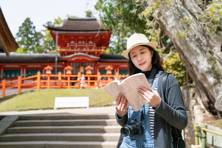 an elegant female tourist reading the information of the temple on her guidebook