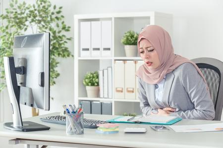 muslimische Geschäftsfrau mit Kopftuch, die Bauchschmerzen hat und Bauch in der Brust trägt. Die Bürodame fühlt sich bei der Arbeit unwohl. Frau im Büroanzug ist krank.