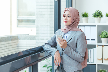 Muslim female manager relying on the window and using smartphone while taking the break. businesswoman lifestyle concept. Office lady shopping online by cellphone and relaxing work.