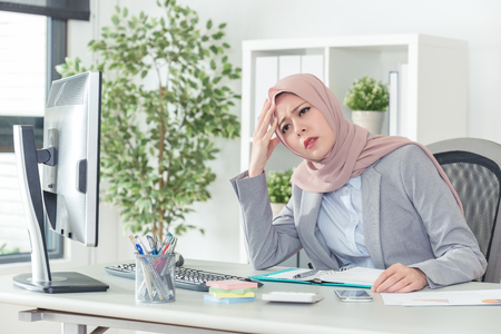 Confident muslim kerchiefed businesswoman having headache and wants to rest while working. Negative work concept. Sad office lady thinking about problems and showing dissatisfaction of career. 스톡 콘텐츠