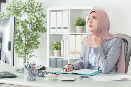 a muslim office lady is confused and thinking about the solution with her chin on her hand. Thinking office worker day dreaming looking up with a sad face in work place. Foto de archivo