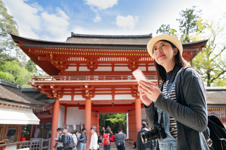 an elegant female traveler using her cell phone, standing in front of the temple and smiling happily