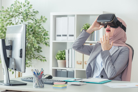 cheerful Muslim office lady relaxing watching 3D movie and opening her mouth because of surprised while having break from work. startup office concept. woman in office suit using 3D viewer. 写真素材