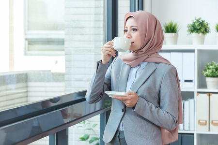 Muslim office lady resting by the window and relaxing drinking coffee. Happy successful businesswoman looking at city view in work window.