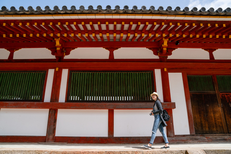 a full length photo of a pretty female photographer relaxing walking in the temple and finding the beautiful view to take photo