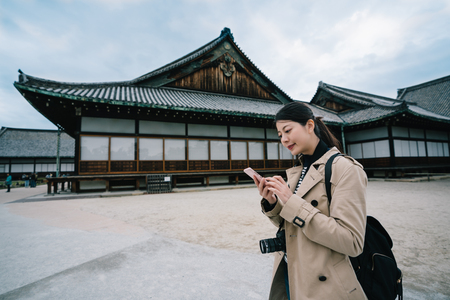 beautiful female traveler finished visiting the temple and checking the next spot on her smartphone. elegant lady counting cost of her trip in Japan by calculator in cellphone. travel in spring holiday concept.