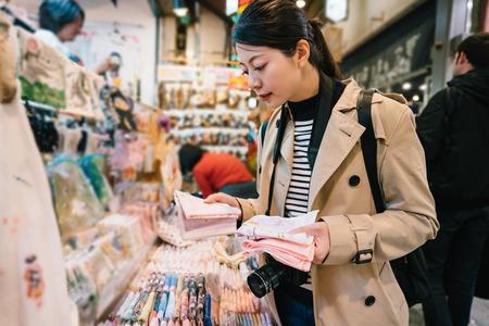 jolie voyageuse choisissant un mouchoir pour sa maman dans le magasin. voyageur élégant achetant un souvenir. Bon shopping dans un magasin spécialisé traditionnel sur le marché au Japon.