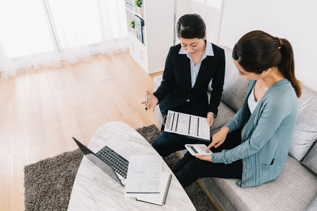 professional female insurance agent introducing assurance planning. businesswoman explaining risk management to housewife. young mom using calculator counting in living room. Stock Photo