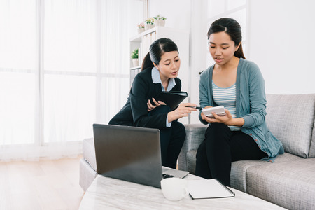 shrewd housewife checking the payment amount of the insurance scheme plan by calculator with the sales. Agent woman presentation and consulting insurance detail to customer.