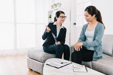 agente de seguros profesional que brinda al cliente su mejor consejo sobre el plan de seguro. abogado ayudando a ama de casa a resolver problemas en casa. estilo de vida de casa moderna y luminosa.