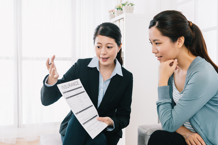 professional insurance agent explaining the assurance planning to the shrewd housewife at home. Female Real Estate agent offer home ownership and life insurance to young woman.