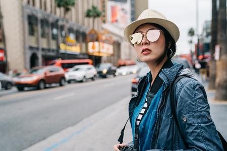 elegant female traveler standing on the street and waiting for taxi to go back to hotel. woman in straw hat and sunglasses looking at the road. cool weather in LA.