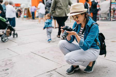 elegant female traveler crouch on the street and taking picture of the ground in a busy street. traveling photographer photography the landmark. Popular super movie stars handprint on the road.