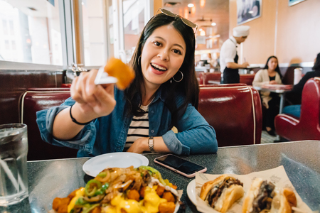 beautiful traveler trying American food in the diner, face to camera smiling joyfully. young tourist showing fried chicken. travel vacation in America.