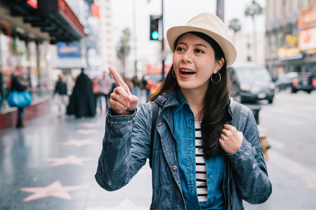 elegant female traveler walking on the street and pointing at the things that attracted her. Travel summer holiday girl enjoying city. Traveling tour in USA.