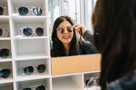 attractive woman trying sunglasses in the glasses shop and looking in the mirror. Asian lady shopping lifestyle. beautiful girl in suitable sunglasses.