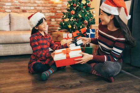 Młoda matka i jej córki na drewnianej podłodze przy choince w domu. atrakcyjne santa dziewczyny wymieniają prezent w salonie w Wigilię Bożego Narodzenia. świętować Boże Narodzenie w domu koncepcji.