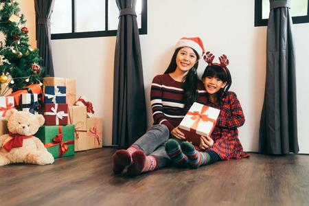Kind mit Geschenk von reizender Mutter. Frohe Weihnachtsdekoration im Haus. attraktive Mädchenkindheit und junge Mutter, die auf dem hölzernen Bodengesicht zum Kameralächeln sitzt.