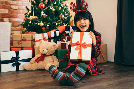 little girl with deer on head got a big present as christmas gift. child holding gift with red ribbon showing big toothy smile. lovely daughter being joyful, fresh and cheerful.