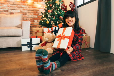 lovely daughter with colorful green socks holding christmas present with red ribbon. Happy little smiling girl with Christmas gift box. Happy Christmas - Kid with gift from santa.